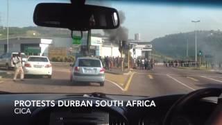 Rioting protestors stone & burn cars & trucks in Durban South Africa
