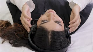Above the head shot of a cute girl lying on her bed and listening to music on black headphones