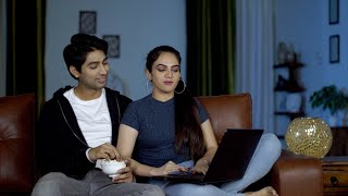 Happy Indian couple using a laptop and eating popcorns together at home in India