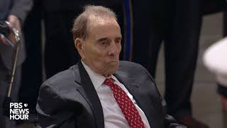 Bob Dole salutes President George H.W. Bush as he lies in state at the U.S. Capitol