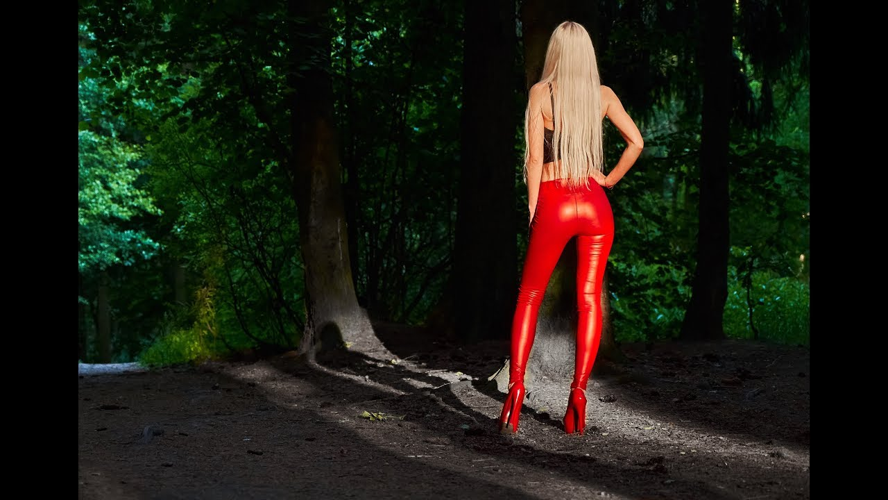 Blonde girl walking in RED leather leggings and high RED heels