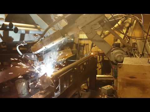 Robots welding rotating pipe for adjustable steel columns.