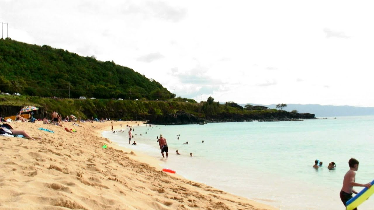 Beach In Hawaii With People Swimming And Relaxing