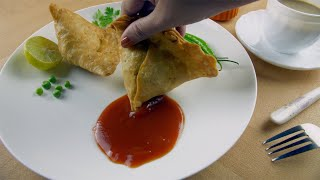 Closeup shot of an Indian woman eating hot and spicy samosa with ketchup - snack time