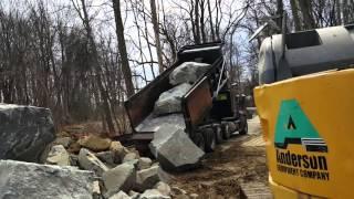 Dump truck dumping huge rocks