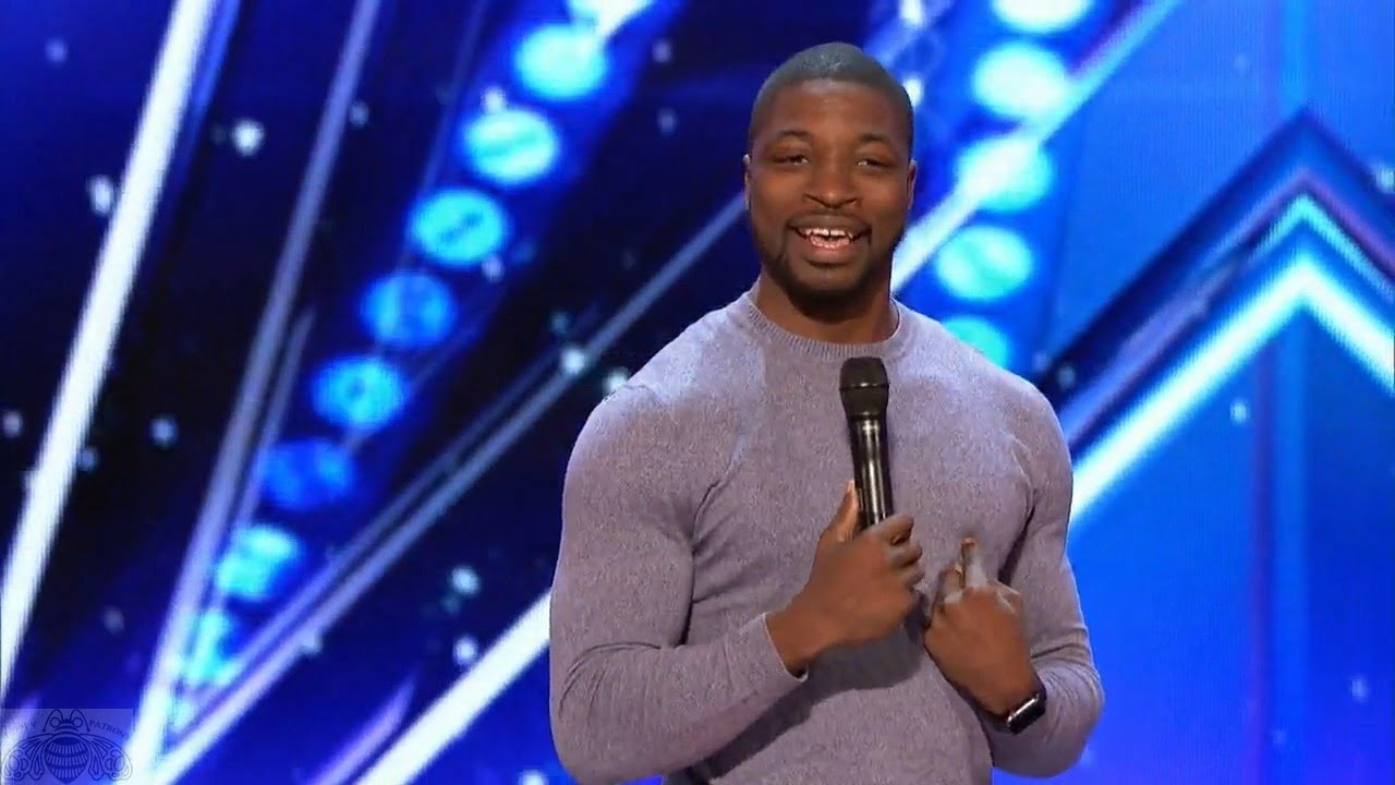 Preacher Lawson standing on AGT stage during his audition holding a mic in his hand