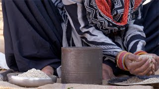 Free footage of a woman putting bajra / millets in iron mortar and pestle