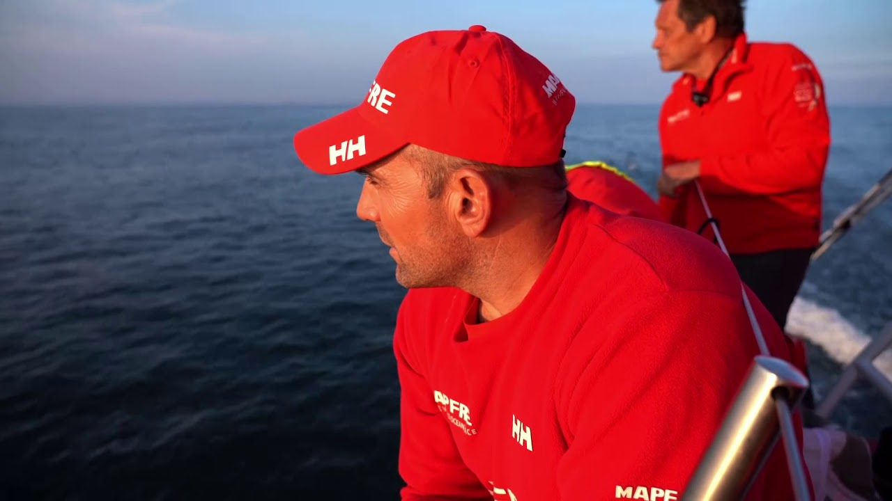Xabi talks in Spanish about the start, competition. Repeats in English. Good start in Cardiff. Tricky conditions. But then the wind dropped to nothing and the guys behind got better wind in the middle of the channel. Could be worse. Now Dongfeng a little ahead of them, Brunel to weather. Now we need to work our way back into the lead. Brunel in glassy conditions. Blair talks strategy. Sophie up the mast to kick battens. Other boats: Vestas, Dongfeng, Scallywag. Drifting. Pablo on the helm. Sophie hosting a sail on the bow, stacking aft. Boat on the horizon ahead of them.