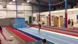 Shirtless Man In Grey Pants Runs And Flips On To Stacked Blue Gym Mats