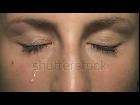 stock footage slow motion tear comes out of an eye and streaks down the cheek