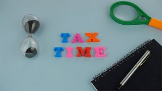 "Racking focus shot of colorful words ""Tax Time"" against the blue background"