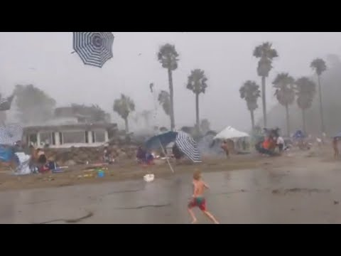 Parents Try to Protect Kids on Beach During Random Weather Occurrence