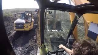 Экскаватор вытаскивает из грязи  самосвал