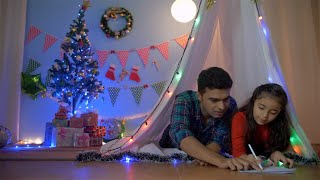 Small Indian girl enjoying drawing with her dad while lying together in the tent - Christmas fun