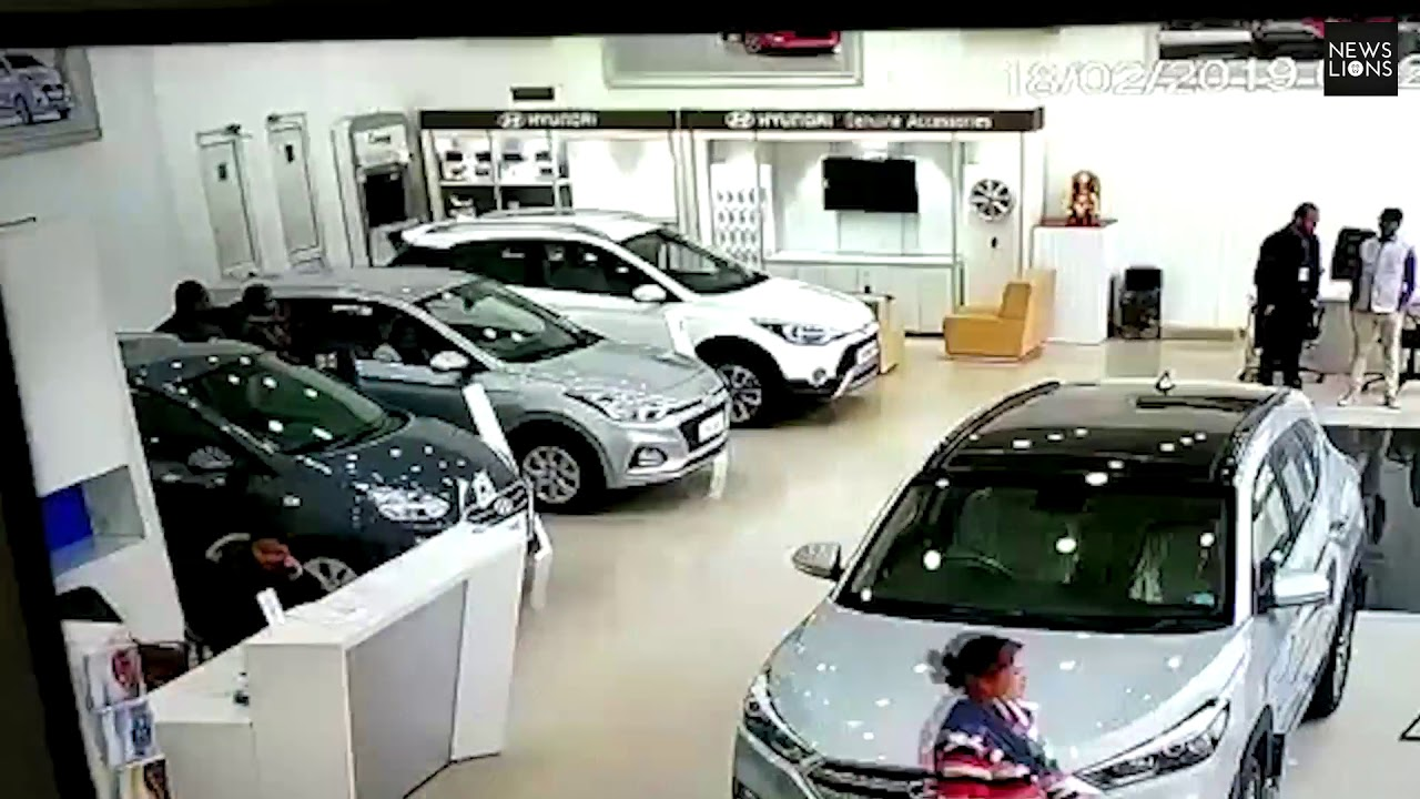 Woman checking out car in showroom, loses control of vehicle crashes through glass wall