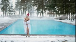 Young blonde woman in bathrobe and red hut near outdoor swimming pool at winter