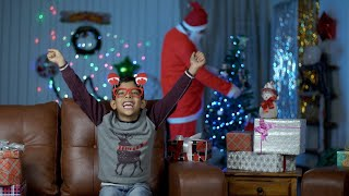 Happy Indian kid is overjoyed after looking at his loving Santa Santa at home with bokeh effect