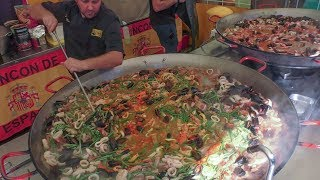 Many Huge Pans Cooking Spanish Paella. Street Food Fair in Italy