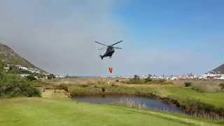 Cape Town Clovelly fire fighting helicopters filling up water buckets from dam on golf course