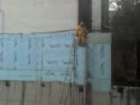 OSHA Violation: Worker stands on column using sledgehammer