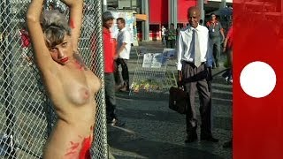 Chained naked to a fence, woman protests against sexism in Brazil