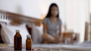 Indian woman taking pills with water in bed -  Health care. Sad and Lonely
