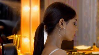 A makeup artist setting hair of a professional model in her vanity van - Movie Shoot