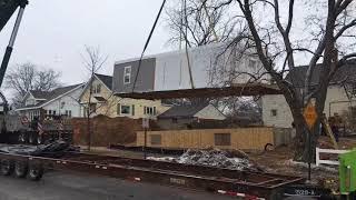 Crane lifts modular home onto foundation