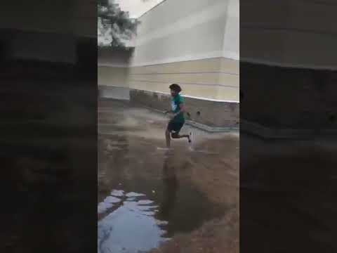 Guys take turns jumping into a big puddle of water.