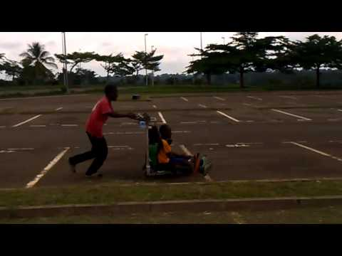 Nsimalen Airport Yaounde summer kids play with airport trolley