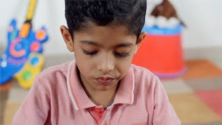 A close shot of young Indian kid giving different facial expressions while playing alone