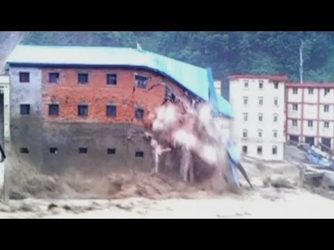 Buildings collapse into raging floodwaters in China