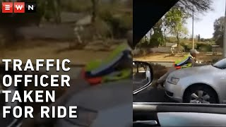 The video of a Gauteng traffic officer hanging onto the bonnet of a fleeing car has gone viral.