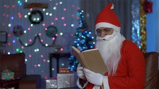 Happy Santa Claus reading a book while sitting on a couch during Christmas time in India