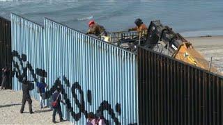 US reinforces border wall in Tijuana as migrants look on