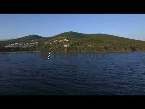Drone flying from sea to the shore with houses on waterfront, Greece