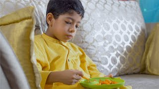 Cute Indian boy eating french fries with ketchup at home
