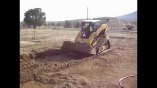 digging a trench & loading dump truck on track loader