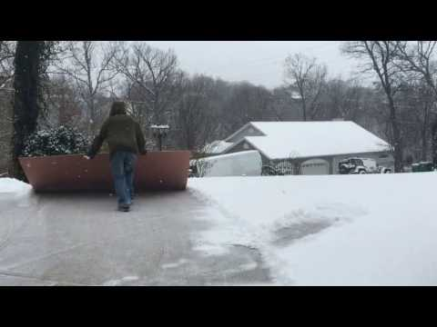 Hack for shoveling snow off driveway with sheet of plywood.