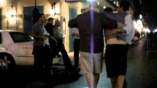Drunk guy with friends helping him walk on Bourbon St