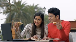 Attractive Indian couple spending college time together in a cafeteria - lifestyle concept