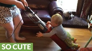 """Baby """"helps"""" mom vacuum the house"""
