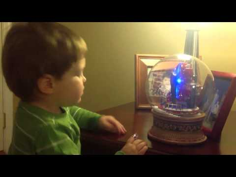 Lucas playing with musical christmas snow globe