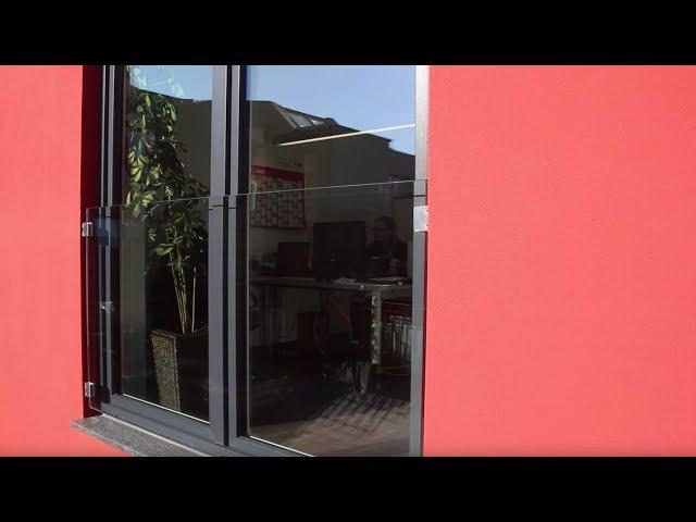 Französischer Balkon aus Glas als Absturzsicherung vor dem tief sitzenden Fenster