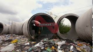 Household dump scattered on the side of a road in India - illegal waste landfill site
