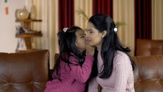 Happy Indian mother and daughter whispering in each other's ears - leisure time