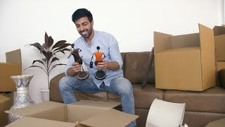 Young Indian man unpacking cartons - moving boxes