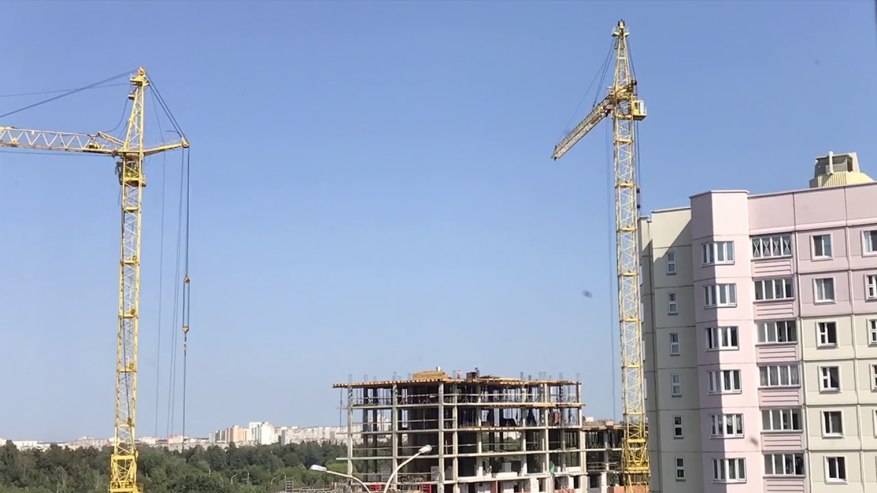 Construction of a building frame made of concrete Works a tower crane,  trucks are moving TimeLapse