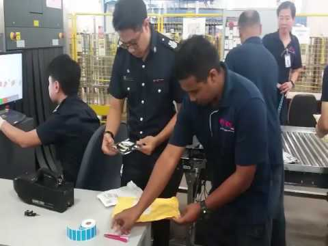 ICA Officers Checking A Suspicious-looking Package At The Singapore Post Mail Processing Centre