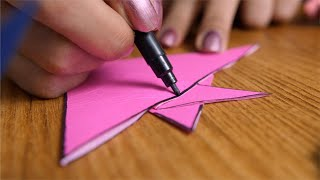 Low angle closeup shot of a girl decorating pink origami fish